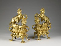 Pair of gilt bronze firedogs of high quality, each comprised of a rearing horse draped with a tasseled and embroidered saddle cloth whose front legs rest of an upright foliate shield with central diaper pattern, possibly after a design by Leonardo da Vinci (1452-1519) for an equestrian monument; the base is sarcophagus shaped with exaggerated, foliate scrolls at each corner, with a central cherub mask resting upon an ornate shield, the legs are likewise comprised of foliate scrolls resting on split, outwardly scrolling feet; with slight variations to the shield upon which the mask rests; the back open and the interior rough as expected.