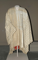 "Voluminous poncho-type garment of narrow strip woven cotton and silk, natural tan silk exterior, lined with red and green striped cotton, with ""eight knives"" and other finely embroided motif"