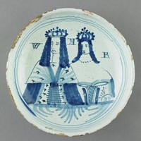 Small tin-glazed earthenware (delftware) dish decorated in cobalt blue with the half-length portraits of King William III and his wife Queen Mary II, who together reigned over the kingdoms of England, Scotland and Ireland beginning in 1689, both depicted in royal robes with crowns, inscribed with the initial W next to William's head and M between the couple, with R to the right of Mary's head, with three thin blue lines around the edge.