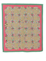 Multi-colored fabrics with 30 intersecting rings separated with four section, diamond patterns. Pink and green outer border. Beige behind rings. Backed with cotton fabric