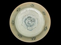 Stoneware dish with a flat bottom, flared wall and squared foot, the pinkish bisque painted with a blue-gray underglaze cobalt design of blossoms and a large central whorled-petal flowerhead