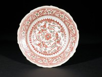 Porcelaneous stoneware dish molded with scalloped edge and fluted cavetto, painted with overglaze red and green enamels, the rim with floral meander band, the center with a design of long-tailed birds and flowers encircled by a serrated border