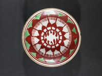 Painted overglaze red and green enamel design of radiating petals, unglazed rim