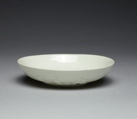 """Small creamy white-colored glazed """"Blanc-de-Chine"""" dish with prunus relief decoration on outer sides, with low foot"""