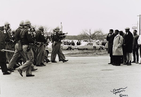 One of five views of Montgomery and Selma, Alabama during the Civil Rights era between 1964 and 1968. This photograph, dating from March 7, 1965, shows white police officers wearing gas masks and carrying batons moving forward on the left towards a group of black men on the right in Selma, Alabama.