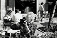 This work is a black and white photograph of an elderly woman putting on her lipstick at an outdoor cafe. She's holding a mirror to see her reflection and has white, short, curly hair and glasses. She's wearing earrings, a watch with a round face, and rings on her middle and index fingers. Her dress is flower patterned with lace around the collar and sleeves.  The table has two glasses, plates, crumpled up napkins and her purse. Behind her a woman and a man are eating lunch. In the back right of the composition, a couple are walking in front of a Banana Republic store with bicycles parked out front.