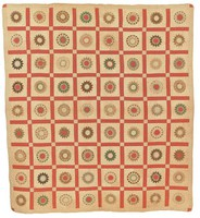 Large square quilt with sunburst and red windowpane design in red, yellow, green, blue, with border in flowered print