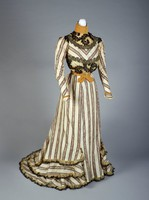 Dress in two parts—bodice and skirt. Long sleeved cream bodice with a high neck. The collar is light orange velvet with knife pleats. Around the waist is the same velvet, which crosses in the front. Across the chest and down the arms, the fabric has diagonal stripes with an orange paisley and floral pattern, bordered by stripes with a black paisley pattern. The section across the chest is outlined with black floral appliques. Across the collarbone and the stomach is sheer beige fabric that is heavily pleated. This fabric has black appliques on it. The cream fabric crosses the mid-back and goes under the arms and across the shoulders. The sheer fabric continues around to the back. The collar becomes higher in the back. There is a thin ribbon of orange velvet with a bow around the wrists. The bodice is fully lined and boned. The floor length skirt made of cream striped fabric striped with an orange paisley and floral design outlined by stripes with a black paisley pattern. Three layers of ruffles are at the bottom, but the ruffles stop at the side. The ruffles are lined with a sheer fabric and black lace. The back has a small train. A cotton underskirt has been attached, but it is not original. Hook and eye closures in the back.