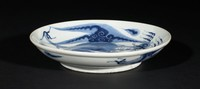 Blue and white plate decorated with a blue dragon in the interior and elongated dragon in blue under the rim in the exterior. Rounded shape with slight bowl profile on a shallow foot with unglazed bottom.