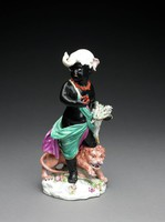 """One of a set of four large figures of soft-paste porcelain representing the """"Four Quarters of the Globe,"""" each depicted as a chubby child dressed in a costume deemed appropriate to his or her region and associated with symbols of the different continents. Africa: the figure of a male child with black skin wearing a green and purple wrap, a bright red coral necklace and an elephant headdress, over his right shoulder is a cornucopia filled with sheaves of wheat, which he supports on his left hip, his right hand grasps a scorpion, symbolic of the mystery and danger of this little known continent, at his feet is a snarling lion, the base decorated with flowers."""