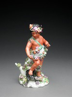 """One of a set of four large figures of soft-paste porcelain representing the """"Four Quarters of the Globe,"""" each depicted as a chubby child dressed in a costume deemed appropriate to his or her region and associated with symbols of the different continents.America: the figure of a male Caribbean native child with red skin wearing a colorful feathered costume and headdress and carrying a quiver of arrows slung over his right shoulder, his left hand holds a bow, under his right foot and resting against a stump decorated with flowers is a small green caiman with open mouth."""