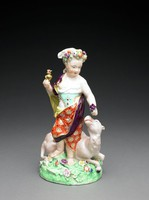 """One of a set of four large figures of soft-paste porcelain representing the """"Four Quarters of the Globe,"""" each depicted as a chubby child dressed in a costume deemed appropriate to his or her region and associated with symbols of the different continents.Asia: the figure of a female child wrapped in loose-fitting silks trimmed with gold and wearing a jeweled bodice, her headdress is decorated with exotic fruits and flowers, in her right hand she holds a gilt censor or incense burner, her left hand clutches a small bouquet of precious spices, at her feet lies a recumbent camel with upturned head on a green grassy ground decorated with flowers."""