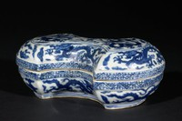 An ingot shaped box decorated with dragons chasing a flaming pearl
