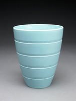 Tall, simple, tapered vase of cream-colored earthenware covered with a matt turquoise glaze, the body engine turned with parallel lines that encircle it, dividing it into five sections