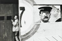 The black-and-white photograph shows the inside doors of the Valencia arena from the bull's vantage point. The image contains the head of male attendant wearing a hat and spectacles to the right of a door marked with the number 7. At left, the blurry figure of a man looks back toward the camera.