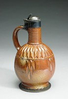 Small brown stoneware jug of bottle shape on slightly flared foot, the body incised with a diamond pattern, the neck turned, with large loop handle, set with silver mounts on foot and neck forming a hinged lid (possibly of later date)