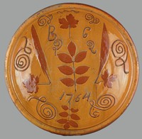 """Deep dish of red earthenware (redware) with a brownish-orange lead-based glaze, the interior with a pattern of individual, incised scrolls and squiggly lines around the border, in the middle a large impressed leaf motif surrounded by four other impressed leaves; below the center leaf the date """"1764"""" and above the initials """"B C."""""""