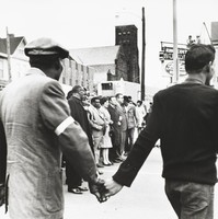 This black-and-white photograph shows a black man and a white man joining hands before a group of demonstrators.