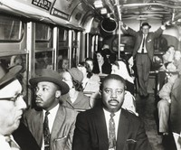 The black-and-white photograph shows Dr. Martin Luther King (at left) and Rev. Ralph Abernathy (at right) riding a desegregated bus in Montgomery, Alabama in December 1956.