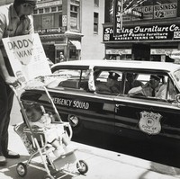 """The black-and-white photograph shows a black man pushing a stroller and carrying a sign that reads, """"Daddy, I Want To Be Free Too."""" The man looks back toward Memphis policemen who look on from their car."""