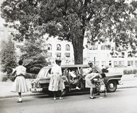 This photograph shows several black girls, escorted by a member of the U.S. Army, getting out of a car to go to school.