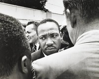 This black-and-white photograph captures a portrait of Dr. Martin Luther King as he is stopped by police. King looks to his right with a furrowed brow. The back of a policeman appears in the foreground.