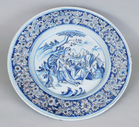 Large round faience charger, the ground glaze with a bluish tinge, painted in shades of light and dark blue enamel with manganese, in the center well a scene of the Holy Family at rest under a tree, on the left is a seated Mary holding the draped Christ Child, on the right is Joseph seated on a rock and turned toward Mary and the Child, holding a walking stick in his hand, on the left is a second walking stick and pack leaning against a rock, in the background a landscape with mountains and a distant town, the rim with a wide band of naturalistic flowers and foliage, around the well and on either side of the floral band are narrow bands of light blue enamel, the figures and flowers are outlined in manganese; the underside of the rim is decorated with a pattern of lines and curves in dark blue enamel.