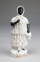 """Creamware flatback figure of Aunt Chloe from """"Uncle Tom's Cabin"""" standing in full figure on a round base, her arms, face and shoes are glazed black, otherwise her two-piece dress and headscarf as well as the basket she holds in her left hand are white and picked out in bronze lustre, with the name AUNT CHLOE written in bronze script on the front of the base."""