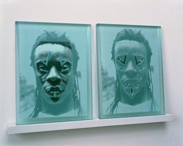 Two transparent glass panels installed side-by-side on a narrow wall-mounted wood shelf. The panels' tops lean against the wall. Affixed to the back of each panel are identical black and white photographic headshots of the artist. Superimposed over the artist's face are imprints of an iron's faceplate. Over the left hand portrait the iron's faceplate is rendered transparent and the perforation holes are opaque; the reverse is true of the right hand portrait.