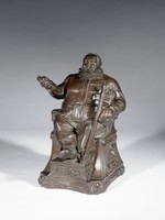 "Large, cast iron tobacco box in the form of a seated, bearded Sir John Falstaff wearing sixteenth-century garb with a large belt and ruffled collar in a scene from Shakespeare's  ""Henry IV"" (act 2, scene 4) in which Falstaff pulls his dagger and proclaims ""…this chair shall be my state, this dagger my scepter…!""  Falstaff is seated in an armchair whose armrests end in goat's heads, below the chair on either side is a bearded male mask; Falstaff's crossed feet rest on a small stool, the chair and stool rest on a base decorated with scrolls; his right arm is raised and his hand holds the handle of his dagger (the blade is broken off); his left arm rests on the chair's armrest while his left hand supports a long sword, which rests against his knee. The upper torso is hinged and opens to reveal the interior of the tobacco box."