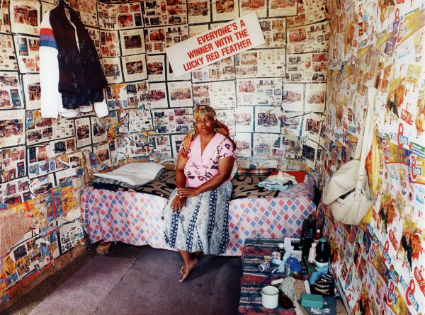 """""""Untitled"""" is a large-scale color photograph of a black South African woman within a domestic interior. The three walls of the room visible in the photograph are papered in newspaper and circular advertisements for food, furnishings and other domestic products. Centered in the photograph is the woman sitting on her bed, which rests against the wall. She sits casually, with her feet crossed and one hand resting comfortably atop the other, and gazes directly at the camera with an alert but relaxed expression. The vibrant colors and patterns of her attire vie with the bed's diamond-patterned counterpane and the busy wall treatment. Pieces of gray carpeting cover the floor. A table in the foreground holds a radio, grooming products, a tin mug, and assorted papers. Above the table a purse and plastic shopping bag hang from a nail; hanging from another nail on the wall to her right are two jackets on hangers. Above and behind her on the wall is a white sign with red lettering that reads, """"Everyone's a Winner with the Lucky Red Feather."""""""