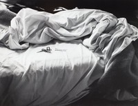 This black-and-white image shows a close-up view of a bed with the sheets and covers pulled back—an unmade bed.