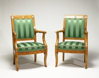 """Two ash and burl ash armchairs, the cabriole front legs end in small scrolls, the arm supports curve inward and likewise end in small scrolls that function as handholds, the arms lathe-turned, terminating in a carved, stylized anthemion motifs where they meet the stile, the back square and each crest rail is set with three green jasper medallions with classical motifs: .1) """"Germany and Turkey with amorini grieving for Elisabeth"""" (from the 1790 series designed for sale in Germany, most of which celebrate the accession and virtues of Leopold II of Austria, who succeeded his brother Joseph II in January 1790. Elisabeth was the favorite niece of Joseph II, who died in February 1790); (probably) """"Cybele, goddess of nature and fertiliy""""; sacrificial scene (unidentified); and .2) """"Fame inscribing a vase to the memory of Elisabeth"""" (from the German series); """"Hercules strangling the Nemean lion"""" (modeled by William Hackwood ca. 1773); """"Germany and Turkey with armorini grieving for Elisabeth"""" (from the German series); the striped green silk upholstery new"""