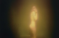 A naked, androgynous figure stands at the center of this image, turned sideways to the camera. The figure's hand partly covers his or her face. The figure is bathed in a golden glow that fades to black at the image's perimeters.