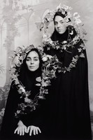 Two women in black garb pose before a studio background; their heads and upper bodies are wreathed in ivy.