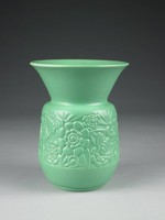Earthenware vase in the Art Deco style covered completely with a mint green matte glaze, the body embossed in the round with a pattern of stylized flowers, foliage, and insects, the long, extended lip flared outward.