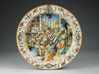 Large, deep polychrome majolica plate in the istoriato style, in the middle with a scene in shades of blue, orange, green, and brown of Julius Caesar in Roman garb with cloak surrounded by Roman townspeople distributing and receiving wine and food within a courtyard defined by architectural structures and columns, probably based on a drawing by Taddeo Zuccaro (1529-66), the border decorated with grotesques on a whitened ground incorporating fantastic birds, part-human creatures, scrolls, stylized urns, and medallions imitating engraved gems, at the top the coat-of-arms of the Petrocchini family of Montelparo, Italy, the outer edge decorated in a modified egg-and-dart pattern; the reverse with a series of bright yellow bands and painted with the inscription SON FATTI DONI AL POPVLO ROMAO