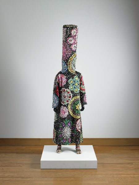 """A life-size one-piece fabric costume with an elongated (36 inch), """"stove pipe"""" head. The costume is adorned with multicolored doilies and buttons. It is presented on a standing mannequin; the mannequin's feet wear a pair of hand-knitted socks that end just above the knee. Only the mannequin's hands are visible. Balancing on the mannequin's shoulders is a metal armature that supports the """"stovepipe""""."""