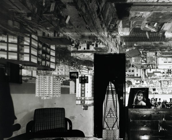 Black and white image of a room within which are visible a chair, a door, against which is propped an ironing board, and a dresser atop which are perfume bottles and a framed headshot of a woman. Upon the room's walls and ceiling is the upside-down image of the surrounding neighborhood, created by the artist by turning the room into a camera obscura.