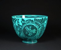 """Known as the """"New Yorker"""" or """"Jazz Bowl,"""" this large and colorful punch bowl, glazed in a rich Egyptian blue, is considered an icon of American Art Deco design. Decorated with streetlights, skyscrapers, cocktails, drunken revelers and musical instruments, including a bass drum head emblazoned with the word """"JAZZ,"""" this vibrant vessel tells the story of a night out on the town. This particular Jazz Bowl is an early example, as the body is fashioned in a perfect parabolic curve. Because the walls of the parabolic bowl sometimes became misshapen in the kiln, later examples were made with a flared rim for additional stability."""