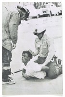 """Press print with caption """"Birmingham Policeman holds down demonstrator seized during racial distubances that shook city. AP Wirephoto, May 8, 1963"""""""