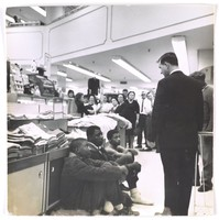 Black and white photograph depicting three young African-American males sitting on the floor of a department store while a white man in a black suit looks down at them. A crowd of white shoppers looks on in the background.