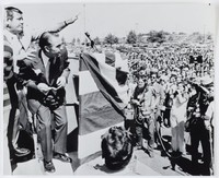 """Press print with caption (verso) """"(WX2)LANDOVER, MD., MAY 12--LOOKING FOR COVER--Ala. Gov. George Wallace ducks behind a bullet-proof podium as one of his aides tries to shield him from flying paper cartons as he spoke to a rally Thursday in Landover, a Washington suburb. Wallace was not hit by the paper cartons and continued his speech. He was campaigning in Maryland for next week's presidential primary. (AP Wirephoto)js60500stf-was)1972"""""""