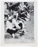 """Press print with caption """"(MRX-8) MONTGOMERY, ALA., MAR. 24-NURSING TIRED AND SORE FEET - Rodney Shaw, Washington, D.C. foreground, bathes his tired and sore feet in a roadside stream while other civil rights marchers rest their feet during a stop today in their march on the Alabama state capitol at Montgomery. The march approached the city limits this afternoon where the demonstrators will make camp before converging on the capitol tomorrow. (APWirephoto) (See AP Wire Story) (wfa 4 1345 stf) 1965"""""""
