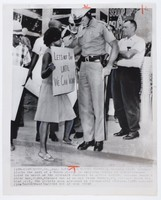 """Press print with caption """"(AXM-1) AMERICUS, GA., Aug. 3-TROOPER BLOCKS PICKET-A Georgia state trooper blocks the path of a Negro picket in Americus Monday as demonstrators tried to march on the sidewalk contrary to police orders. Seconds later a white man, right, slapped out at picket Sammy Rushing, 19, striped shirt behind girl, The pickets were arrested on trespassing charges. (APWirephoto) (jtm/bh30600stf/dm) 1965 SEE AP WIRE STORY"""""""