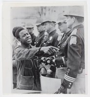 Black and white press print featuring a line of white male state troopers (right) and an African-American male facing them, pointing his right finger and holding a sign in his left hand.