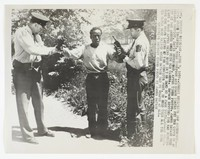 """Press print with caption """"DE-6, Detroit Michigan.. June 7, 1952..Credit Exclusive INP Soundphoto...Mich. State Troopers, Milo Thompson and Duane Thayer put the cuffs on an escaped convict, David Henderson, after Times Photog. James Savage held him at bay armed only with his camera. Savage spotted the man running along a road after being shot in the hand by a farm youth, Donald Frier. Note the knife laying at the convicts feet, he held this all the time his hands were raised while Savage had no weapon at all. Exclusive Detroit Times Photo by James Savage."""""""
