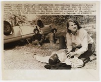 """Press print with caption """"(WAX1)LINCOLNTON, GA., Oct. 23--DEMONSTRATORS WRECKED--Cary Stone, Civil Rights worker, comforts injuried [sic] youth Jimmy Wells who was hurt when the car, background, in which he and six other Negroes were riding spun out of control and overturned near Lincolnton, Ga. Today. Another occupant of the car, Richard Smith, said two white youths chased and harassed the negroes. AP WIREPHOTO"""""""