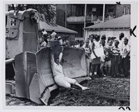 """Press print with caption """"NEGRO WOMAN BLOCKS BULLDOZER / A Negro woman hangs on blade of a bulldozer which was parked at the site of mobile classroom units at 74th Street and Lowe Ave. on Chicago's south side Aug. 2. Demonstration was staged by CORE which contends that Negro pupils should be sent to existing predominantly white schools rather than in temporary classrooms."""""""