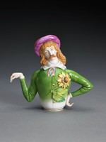 Small, delicate, finely modeled porcelain teapot in the form of on one side a dandy with bangs, long red hair, and a moustache, wearing a kind of pink artist's cap, his head tilted slightly right, his large collar bound with a loose pink tie over a smartly tailored green suit, with a large yellow sunflower on his left breast, his left arm bent and resting on his hip, forming the teapot's handle, his right arm slightly outstretched and bent at the elbow, with his right hand limp and pointed downward, forming the spout; on the other side, the teapot is in the form of a woman sporting a similar hairstyle, her hair also red, wearing a large white ruffled collar, a similar cap on her head, and a large white lily on her right breast over her fitted, green smocked gown, in opposition to her companion, it is her right arm that is bent to form the handle and her left arm is outstretched and bent at the elbow to form the spout; the head is removable, forming the cover, with a band of gilding around the foot.